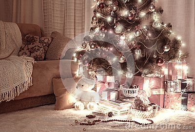Room in dark with illuminated christmas tree, decoration and gifts, home interior at night, red brown toned