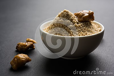 Stock Photo of Asafoetida powder / Hing or Heeng with cake and mortar