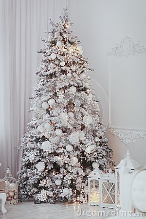 Holiday decorated room with Christmas tree covered with snow and toys. White interior with lights.
