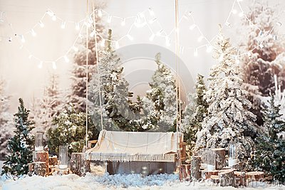 Wooden swing in a snow-covered park or forest with spruce trees and stumps, big candles in glass vases, while snowing