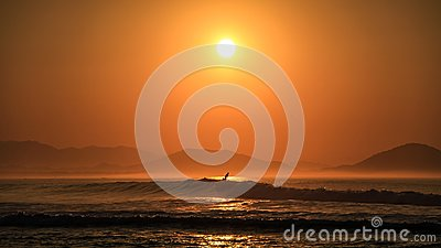 Surfer surfing at sunrise on the beautiful coast of the Chacahua National Park, Oaxaca, Mexico