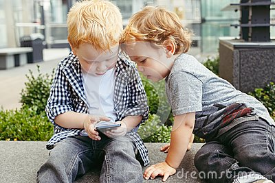 Caucasian toddlers boys sitting together and playing games on cell mobile phone digital tablet