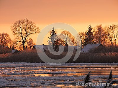River Atmata , homes and snowy trees in sunset colors, Lithuania