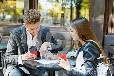 Two young business people using digital tablet on a meeting at coffee shop