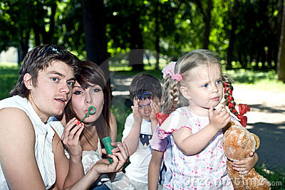 Happy family in park with  bubbles.