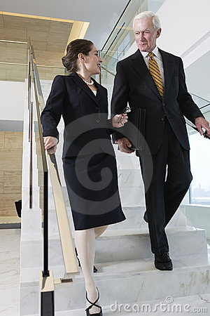 Senior executive with businesswoman talking.