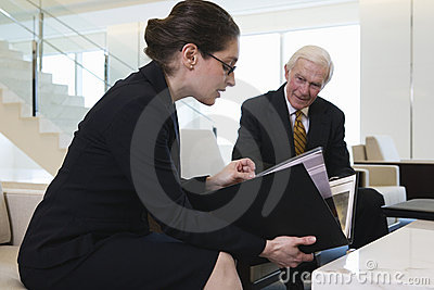 Businesswoman and senior executive in lobby.