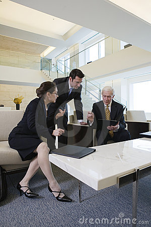 Business team in lobby meeting to review paperwork