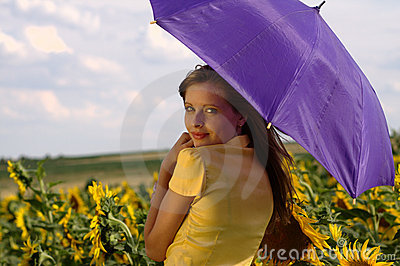 Beauty young woman with umbrella in sunflowers