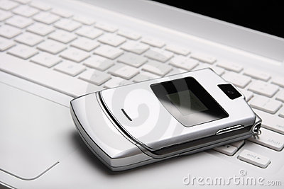 Mobile phone on a white laptop.