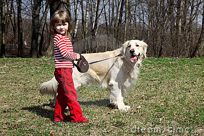 Little girl with big retriever outdoors
