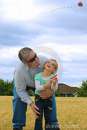 Father and doughter flying kite .