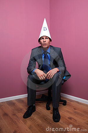 Businessman sat in corner wearing dunce hat