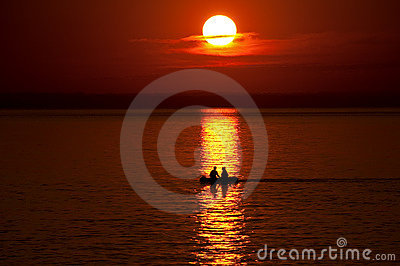 Boat with people against an orange sunset