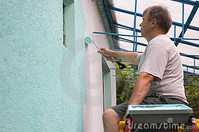 Man painting wall with a roll