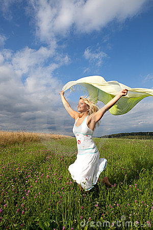 Woman is running on a green meadow