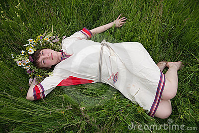 Girl in a camomile  chaplet lying from meadow
