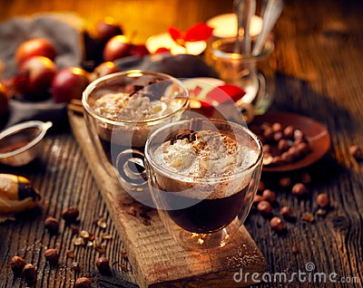 Hot chocolate with whipped cream, sprinkled with aromatic cinnamon in glass cups