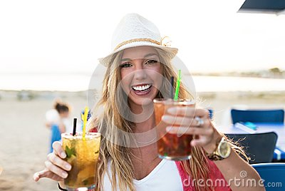 Beautiful young woman drinking refreshment on the beach.