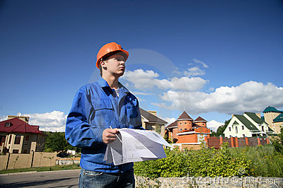 Man in a orange helmet with the plan of construction