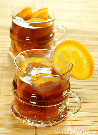 Two glasses with cold tea and fresh oranges