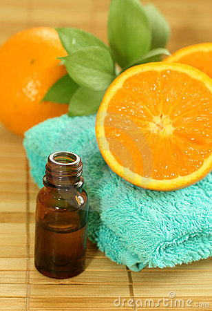 bottle of essence oil, towel and fresh oranges