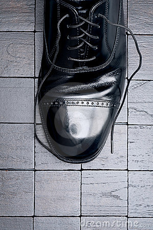 A black leather shoe with laces untied
