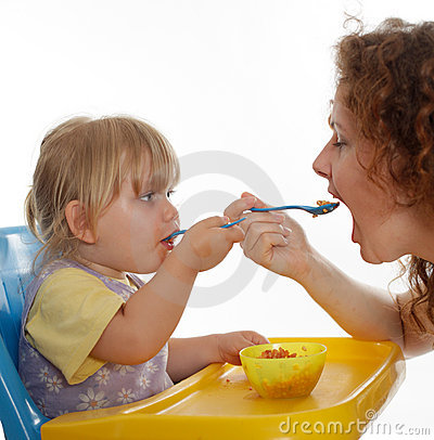 Little girl eating from one pot with woman