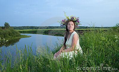 Pretty girl  in flower chaplet against river