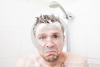 Worried foamed young man after the water in the shower was turned off, looking at the camera.