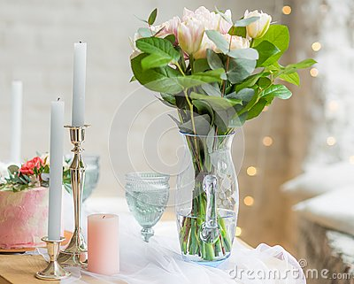 Bouquet of flowers in vase on the table with candles