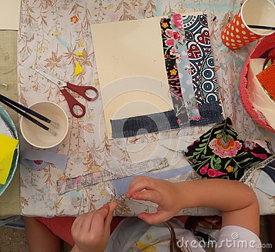 A girl glues and cuts fabric into a picture