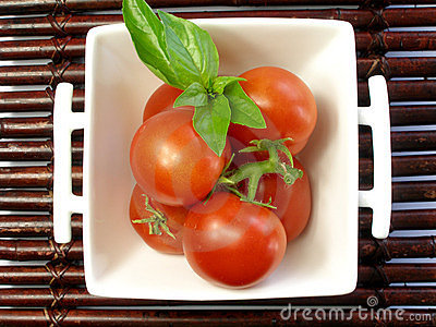 Small tomatoes with a leaf of basil