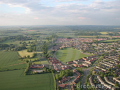 Aerial shot of town in countryside with fields