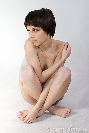 Portrait of girl who sits half naked, looking to t
