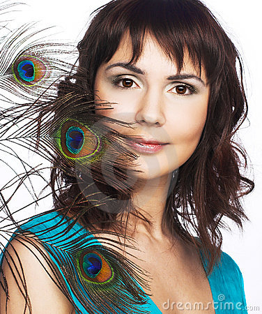 Young woman and peacock feathers