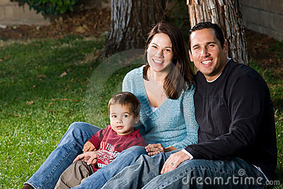 Happy Family Sitting on Grass
