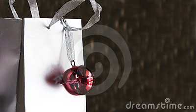 Red jingle bell on silver shopping bag