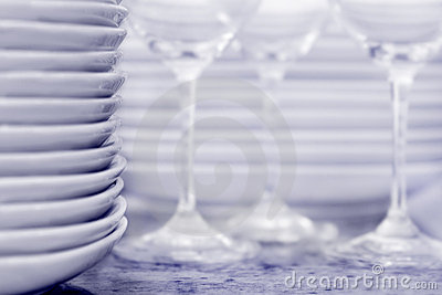 Stack of plates with wineglasses and more plates i