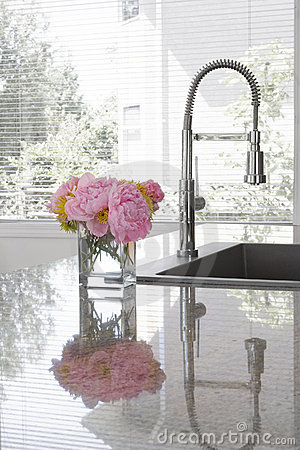 Vase of peonies on sink of modern kitchen
