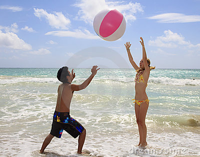 Couple playing with a ball at the beach