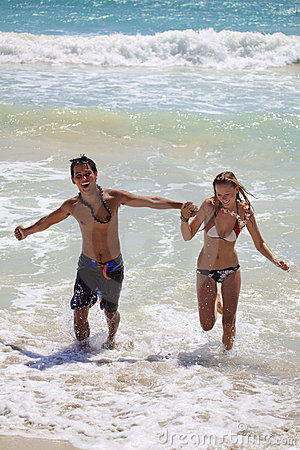 Young couple runs out of the ocean