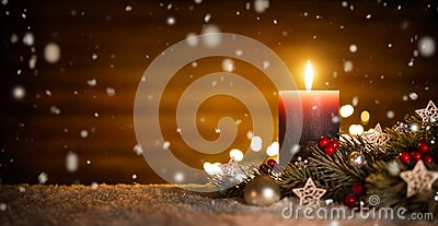 Candle and Christmas decoration with wooden background and snow