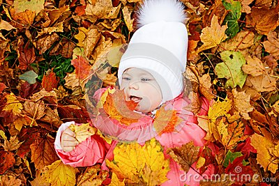 Adorable little baby girl in autumn park on sunny warm october day with oak and maple leaf