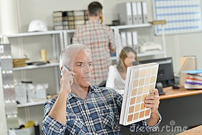 Boss on phone holding colour chart