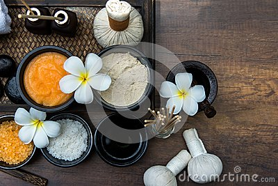 Thai spa composition treatments aroma therapy with candles and Plumeria flowers on wooden table close up.