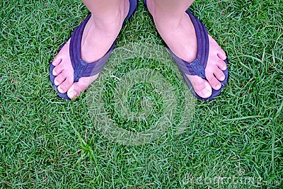 Beautiful woman legs in summer slippers on green grass, foot wom