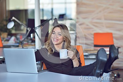 Happy beautiful young business woman sitting and talking on cell phone in office