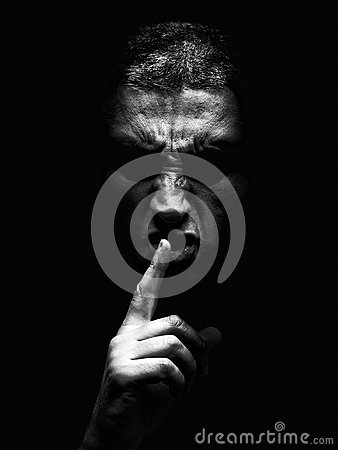 Furious mature man with an aggressive look making the silence sign in a violent and threatening way.