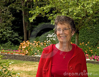 Older Woman Smiling In Garden Setting